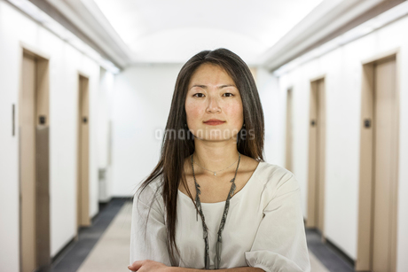 An Asian businesswoman standing alone in her office  space.の写真素材 [FYI02264466]