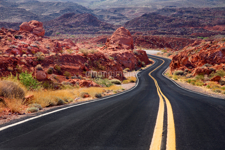 Rural road winding through remote mountain landscape with red rocks.の写真素材 [FYI02264468]