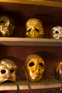 Close up of selection of golden carnival masks on shelves.の写真素材 [FYI02264469]