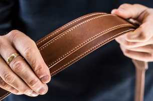 Close up of person holding handmade brown leather camera strap.の写真素材 [FYI02264471]