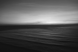 The water surface of the ocean at dusk, black and white, ripples and waves.の写真素材 [FYI02264473]