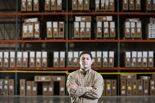 A Hispanic male warehouse worker standing next to racks of boxed products in a distribution warehousの写真素材 [FYI02264476]