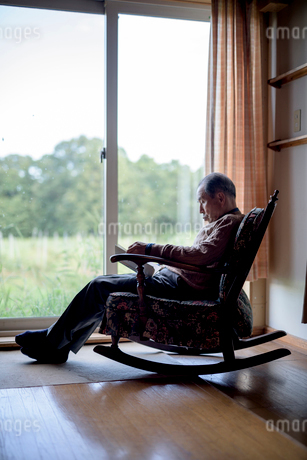 Elderly man sitting in rocking chair by a window, reading book.の写真素材 [FYI02264487]