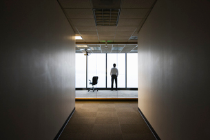 A businessman standing next to a window at the end of a long hallway.の写真素材 [FYI02264490]