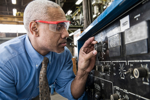 Black man factory owner checking gauges on a piece of welding equipment.の写真素材 [FYI02264492]