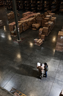 Two warehouse workers going over inventory sheets of products in a distribution warehouse.の写真素材 [FYI02264495]