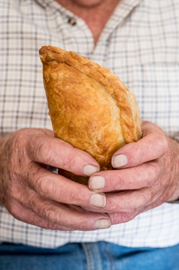A man holding a fresh homemade pasty with a crimped edge, a regional specialityの写真素材 [FYI02264501]