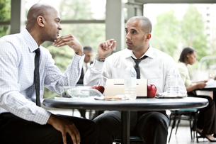 A black businessman and a middle eastern businessman having a business lunch.の写真素材 [FYI02264503]