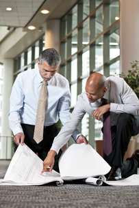 Two men going over plans for a new office space while kneeling on an office carpet.の写真素材 [FYI02264504]