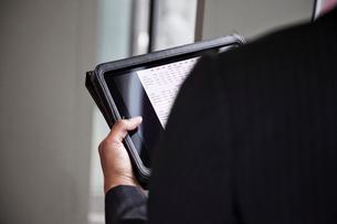 A closeup of hands holding a notebook computer.の写真素材 [FYI02264505]
