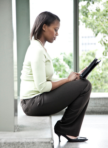 A black businesswoman working on a notebook computer while sitting on a window ledge in a conventionの写真素材 [FYI02264512]