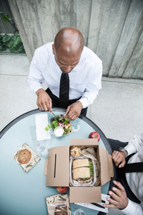 Looking down on a black businessman having lunch with a business associate.の写真素材 [FYI02264518]