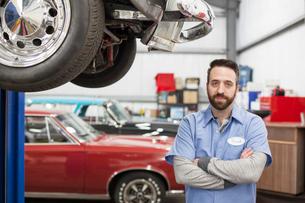 A portrait of a Caucasian mechanic in his classic car repair shop.の写真素材 [FYI02264525]