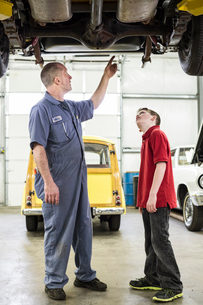A Caucasian senior male car mechanic talks to his grandson about car repairs in a classic car repairの写真素材 [FYI02264532]