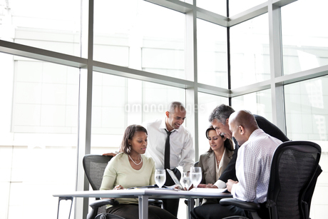 A mixed race group of male and female business people in a meeting at a conference table next to a lの写真素材 [FYI02264533]