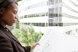 A black businesswoman looking at plans for a new office while standing in front of a large office wiの写真素材 [FYI02264534]