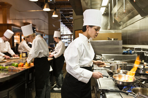 A crew of chef's working in a commercial kitchen, with a black chef in the foreground sauteing vegetの写真素材 [FYI02264535]