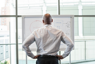 View from behind of a businessman standing at a white board in front of a large window.の写真素材 [FYI02264537]