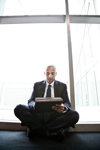 Middle eastern businessman working on a notebook computer and sitting next to a window in a conventiの写真素材 [FYI02264543]