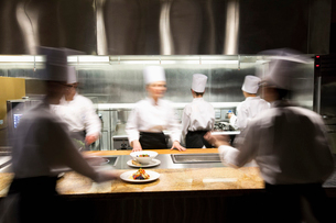A blurred view of a crew of  chefs working around a commercial kitchen.の写真素材 [FYI02264544]