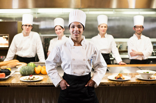 A portrait of a black female chef and her team of chefs in the background of a commercial kitchen,の写真素材 [FYI02264551]