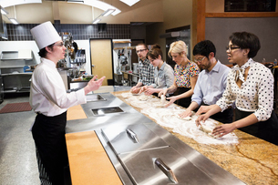 A Caucasian male chef teaching a cooking class for a mixed race grope of students in a commercial kiの写真素材 [FYI02264556]