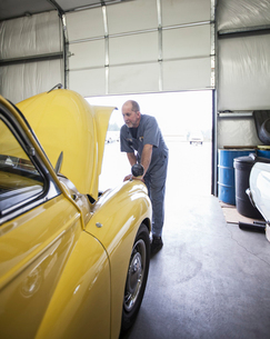 A mechanic looking under the bonnet of a bright yellow Morris Minor English classic car.の写真素材 [FYI02264557]