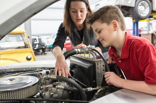 A Caucasian female car mechanic talks to her young son about a car engine in a classic car repair shの写真素材 [FYI02264560]