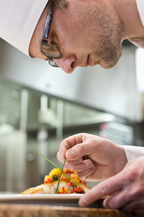 A Caucasian male chef putting the finishing touches on a plate of fish in a commercial kitchen.の写真素材 [FYI02264561]