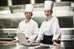 A portrait of a mixed race pair of chefs working with a laptop computer in a commercial kitchen.の写真素材 [FYI02264563]