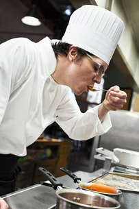 A Caucasian male chef tastes a sample of the sauce he is making in a commercial kitchen,の写真素材 [FYI02264570]