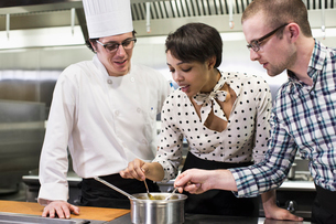 A Caucasian male chef teaching a cooking class for a mixed race grope of students in a commercial kiの写真素材 [FYI02264572]