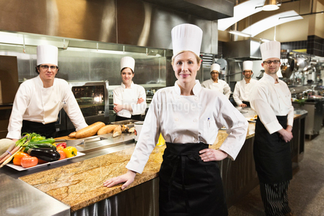 A portrait of a Caucasian female chef and her team of chefs in the background.の写真素材 [FYI02264573]