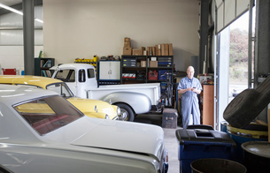 A mechanic standing in an auto repair shop, with a line of classic cars.の写真素材 [FYI02264580]