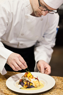 A Caucasian male chef putting the finishing touches on a plate of fish in a commercial kitchen.の写真素材 [FYI02264595]