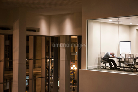 A view looking into a conference room at night  with a single businessman asleep at a conference tabの写真素材 [FYI02264597]