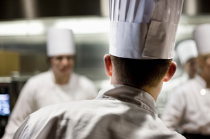 A closeup view from behind of a chef  wearing a toque hat in a commercial kitchen.の写真素材 [FYI02264599]