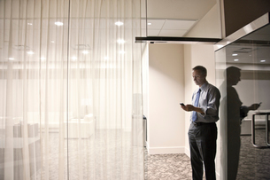 A view looking into a conference room  of a businessman on his cell phone.の写真素材 [FYI02264601]