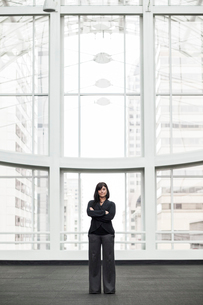 A portrait of a young businesswoman standing in front of a window in a large convention centre lobbyの写真素材 [FYI02264607]