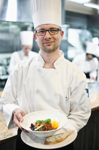 A Caucasian male chef presenting a finished plate of fish in a commercial kitchenの写真素材 [FYI02264608]