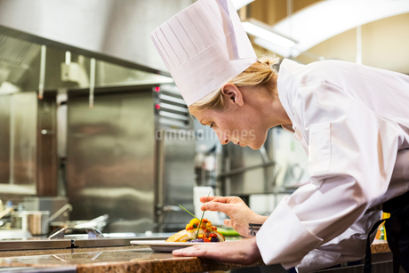 A Caucasian female chef putting the finishing touches on a plate of fish in a commercial kitchen.の写真素材 [FYI02264622]