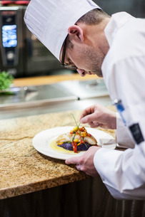 A Caucasian male chef putting the finishing touches on a plate of fish in a commercial kitchen.の写真素材 [FYI02264626]