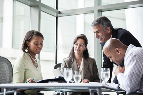 A mixed race group of male and female business people in a meeting at a conference table next to a lの写真素材 [FYI02264627]