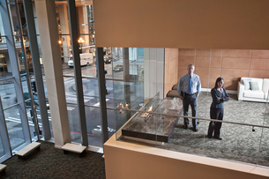 A large building, lobby, view looking into an office with glass walls, two business people talking.の写真素材 [FYI02264631]