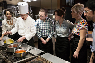 A Caucasian male chef teaching a cooking class for a mixed race grope of students in a commercial kiの写真素材 [FYI02264635]