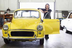 A Caucasian female stands next to her old car in a classic car repair shop.の写真素材 [FYI02264638]