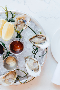 Platter of oysters on ice with lemons and saucesの写真素材 [FYI02264645]
