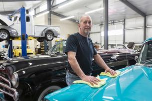 A Caucasian senior male car mechanic in his classic car repair shop.の写真素材 [FYI02264649]