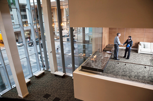 A large building, lobby, view looking into an office with glass walls, two business people talking.の写真素材 [FYI02264653]