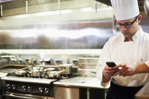 A Caucasian male chef checking his cell phone in a commercial kitchen,の写真素材 [FYI02264657]